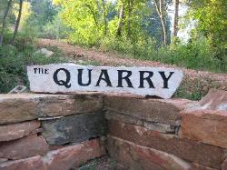 The road to the quarry is marked by a retaining wall and monument.