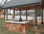 stone veneer grill table and covered patio