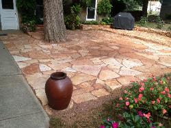rusty sandstone patio with planter and outdoor grill