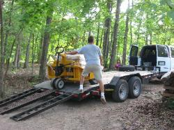 Pallets of stone are unloaded using a rough-terrain pallet jack lowered by a heavy-duty winch.